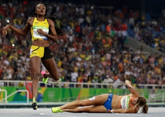 Second placed Netherlands' Dafne Schippers lies on the ground after falling over the finish line as Elaine Thompson from Jamaica, left, wins the gold in the women's 200-meter final during the athletics competitions of the 2016 Summer Olympics at the Olympic stadium in Rio de Janeiro, Brazil, Wednesday, Aug. 17, 2016. (AP Photo/David J. Phillip)